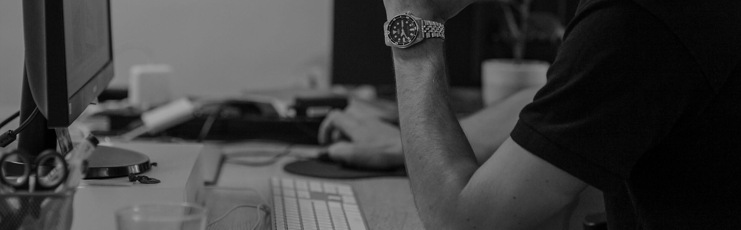 Muž pracuje na PC hodinky na ruke