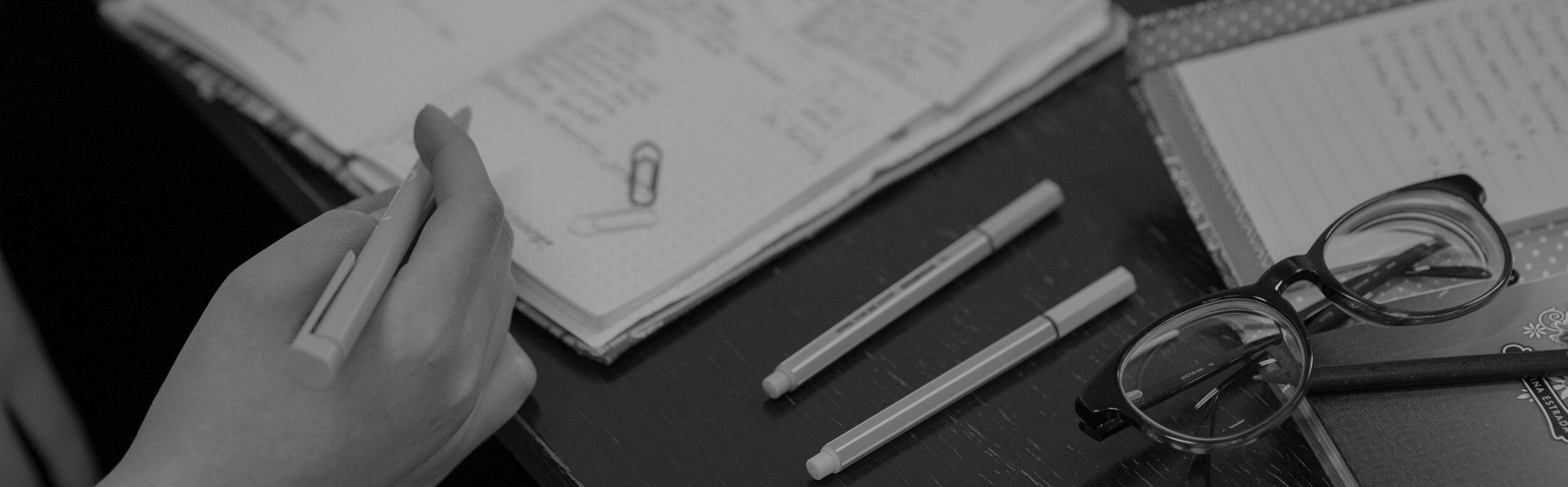 Ženská ruka píše okuliare na stole zápisníky