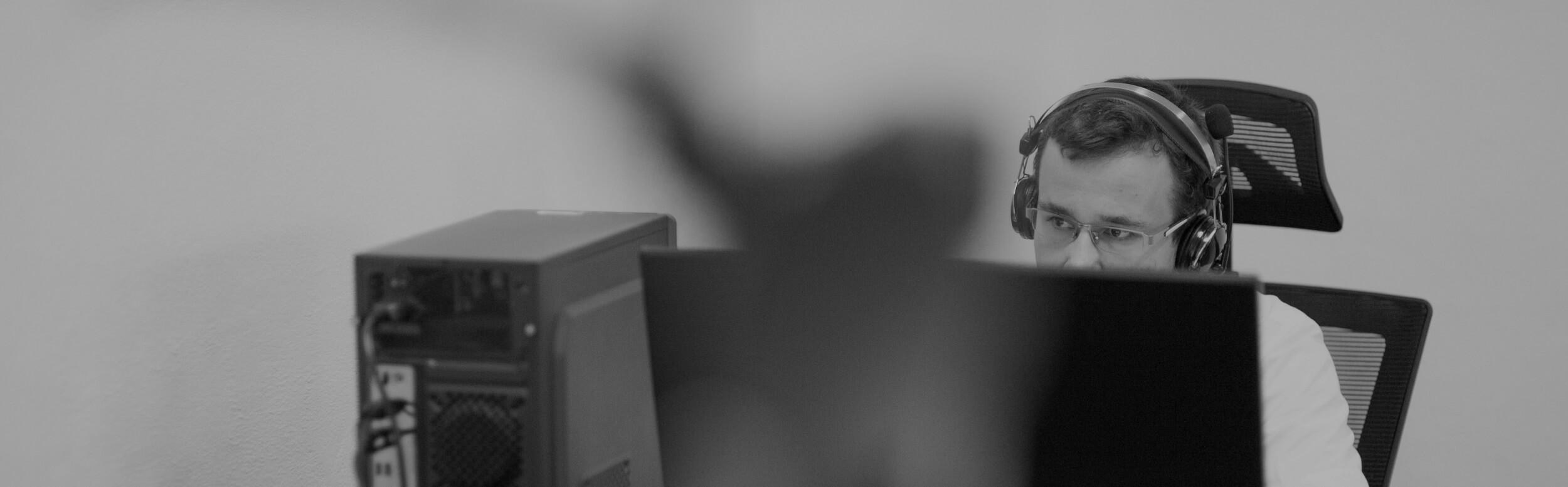 Muž so slúchadlami pracuje za počítačom