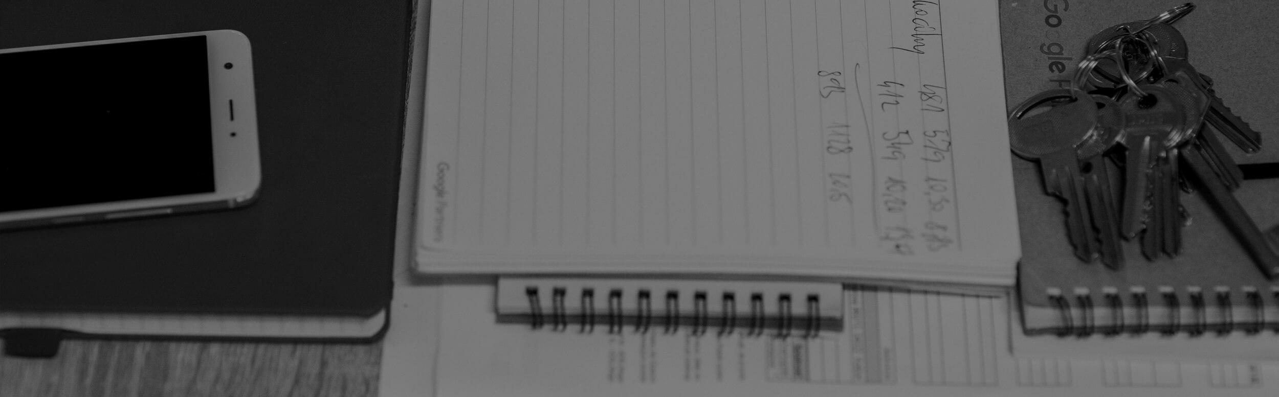 Zápisník s údajmi, mobil, kľúče na stole