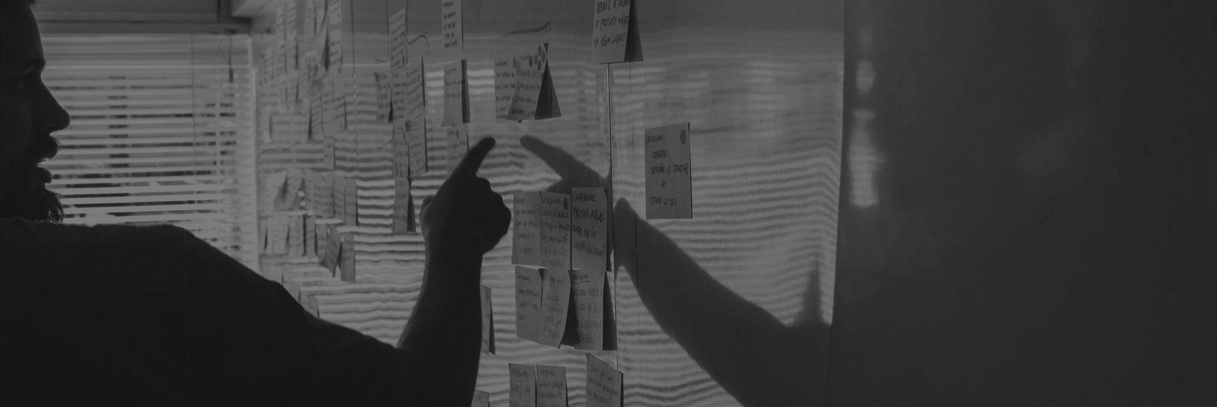muž ukazuje na tabuľu s papierikmi