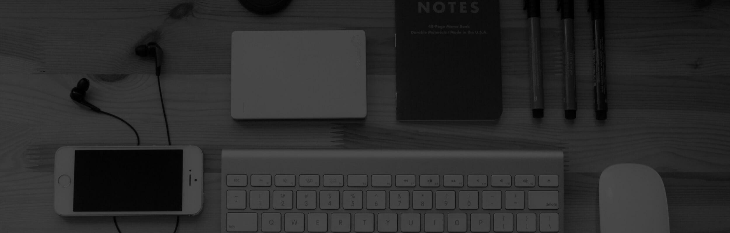 mobil, klávesnica, zápisník a perá na drevenom stole