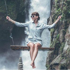 usmievajúca žena v košeli na drevenej hojdačke v prírode pri vodopáde